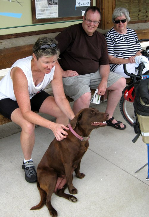 Laura, Rick Karr (Laura's brother who drove the sag wagon) and Jean with a friendly dog at a stop along the trail