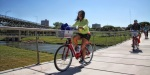 Volunteers ride across the Phyllis Tilley Bridge to deliver bike-share bikes to a docking station in Trinity Park